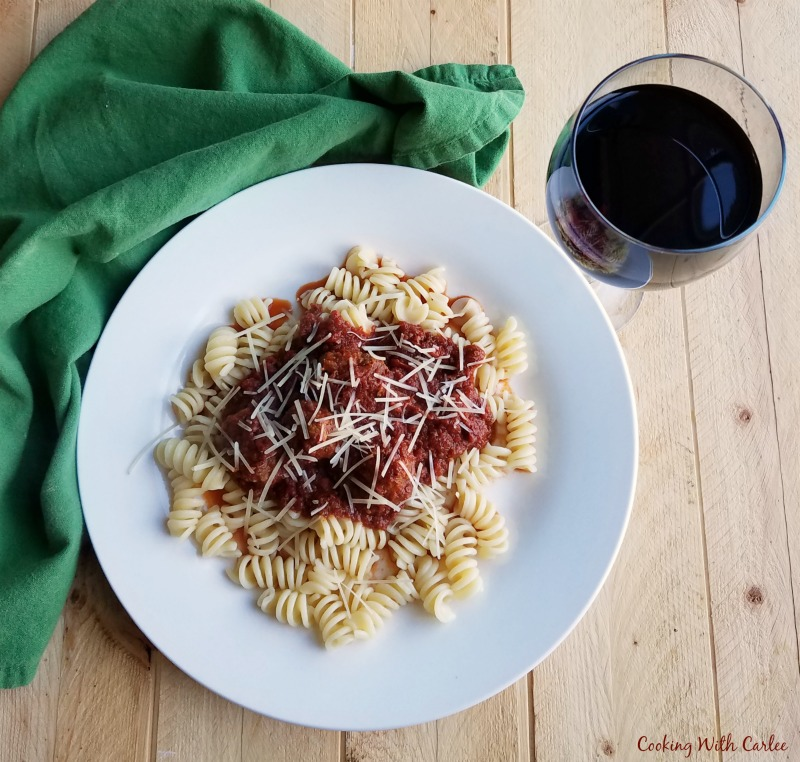 plate of rotini topped with meatballs and tomato sauce with a glass of red wine
