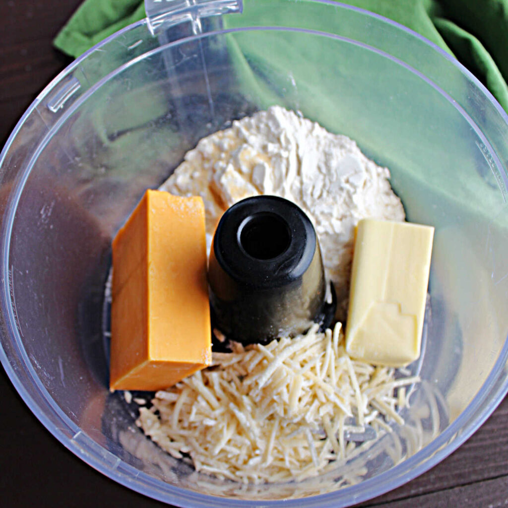 Cheese, butter and flour in food processor ready to be made into dough.