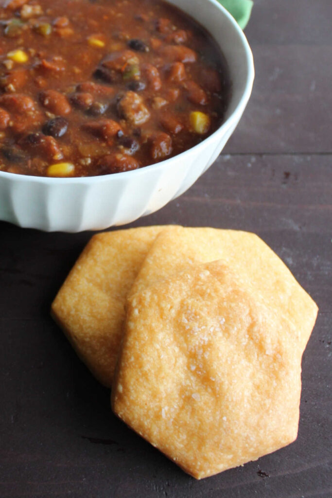 large homemade cheese crackers next to bowl of chili.