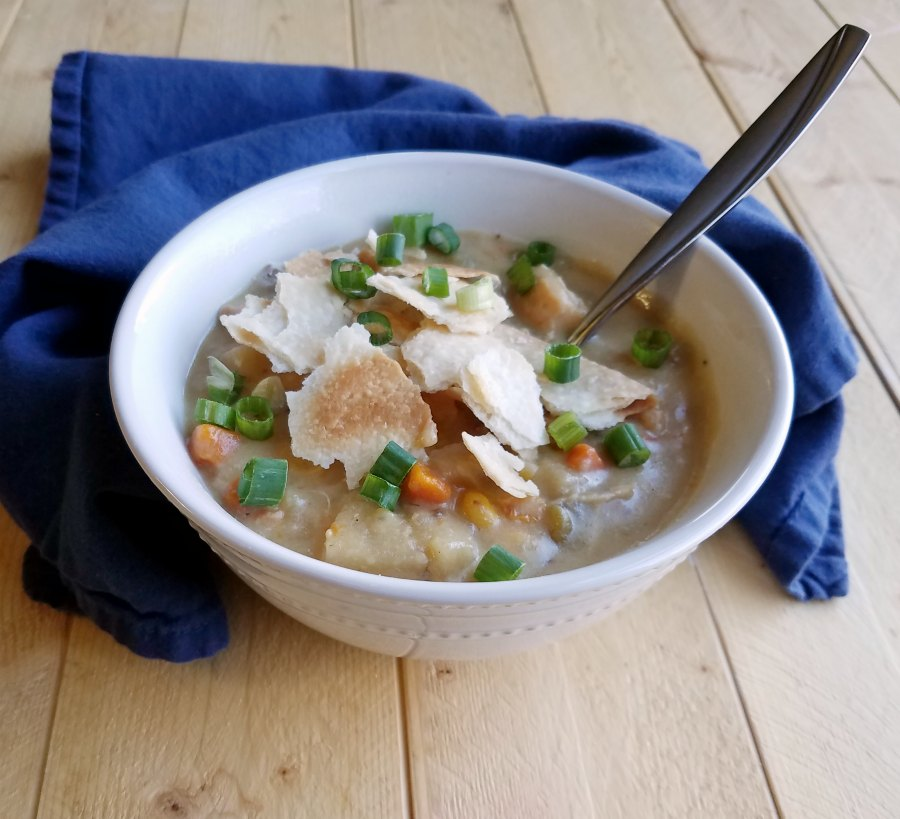 Bowl of creamy chicken pot pie soup topped with big of pie crust and scallions.