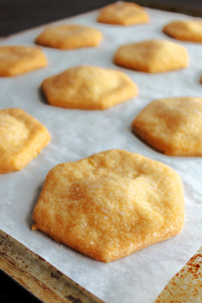 Freshly baked cheese crackers on parchment paper lined pan.