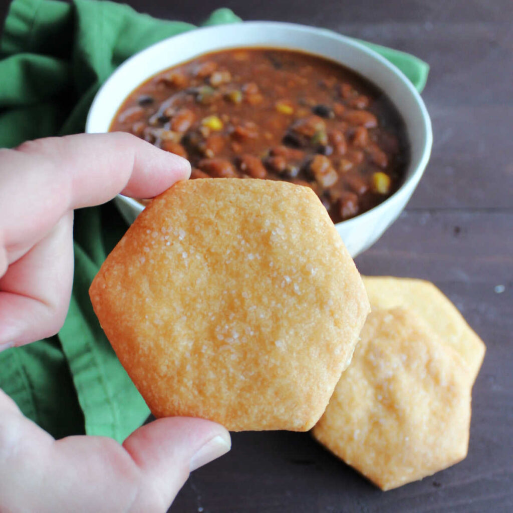 Hand holding cheese cracker in front of bowl of chili.