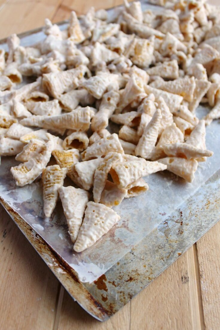 White trash snack mix made of white chocolate coated bugles and nuts on wax paper cooling.