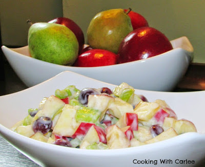 bowl of fruit salad dressed in honey yogurt dressing with bowl of apples and pears in background.
