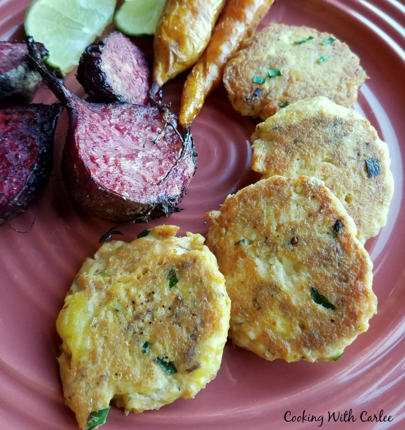 salmon patties with roasted beets and slices of lime