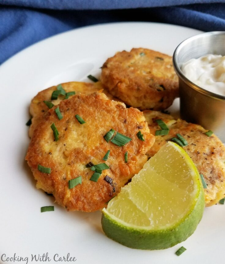 salmon and potato cakes with lime wedge and chives