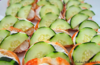 lined up slices of baguette with ranch cream cheese spread and halved cucumber slices on them