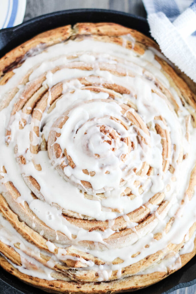 Close up of skillet full of large cinnamon roll with white glaze.