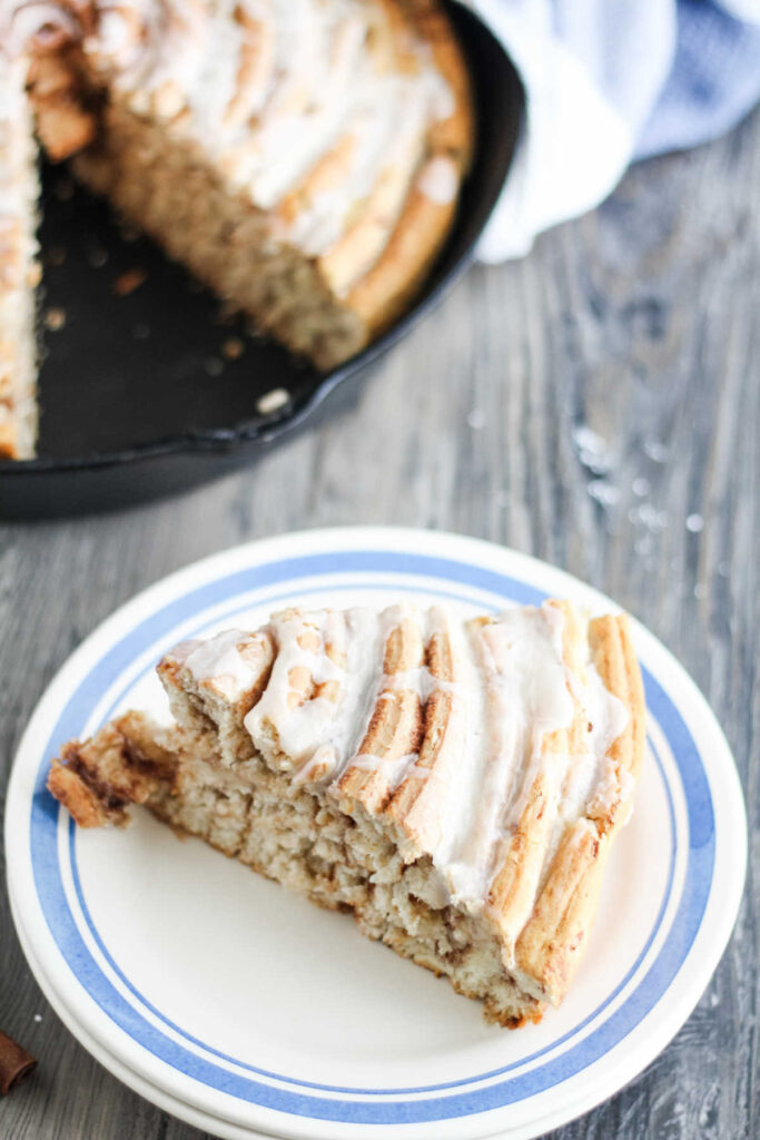 slice of giant cinnamon roll cake with lots of layers on plate ready to eat.