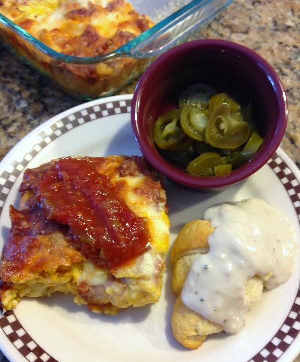 tater tot breakfast casserole topped with salsa, small bowl of jalapenos and a gravy covered crescent roll on plate.