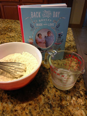 Flour mixture in bowl with whisk, ice water in measuring cup and cook book, ready to make pie crust pastry.