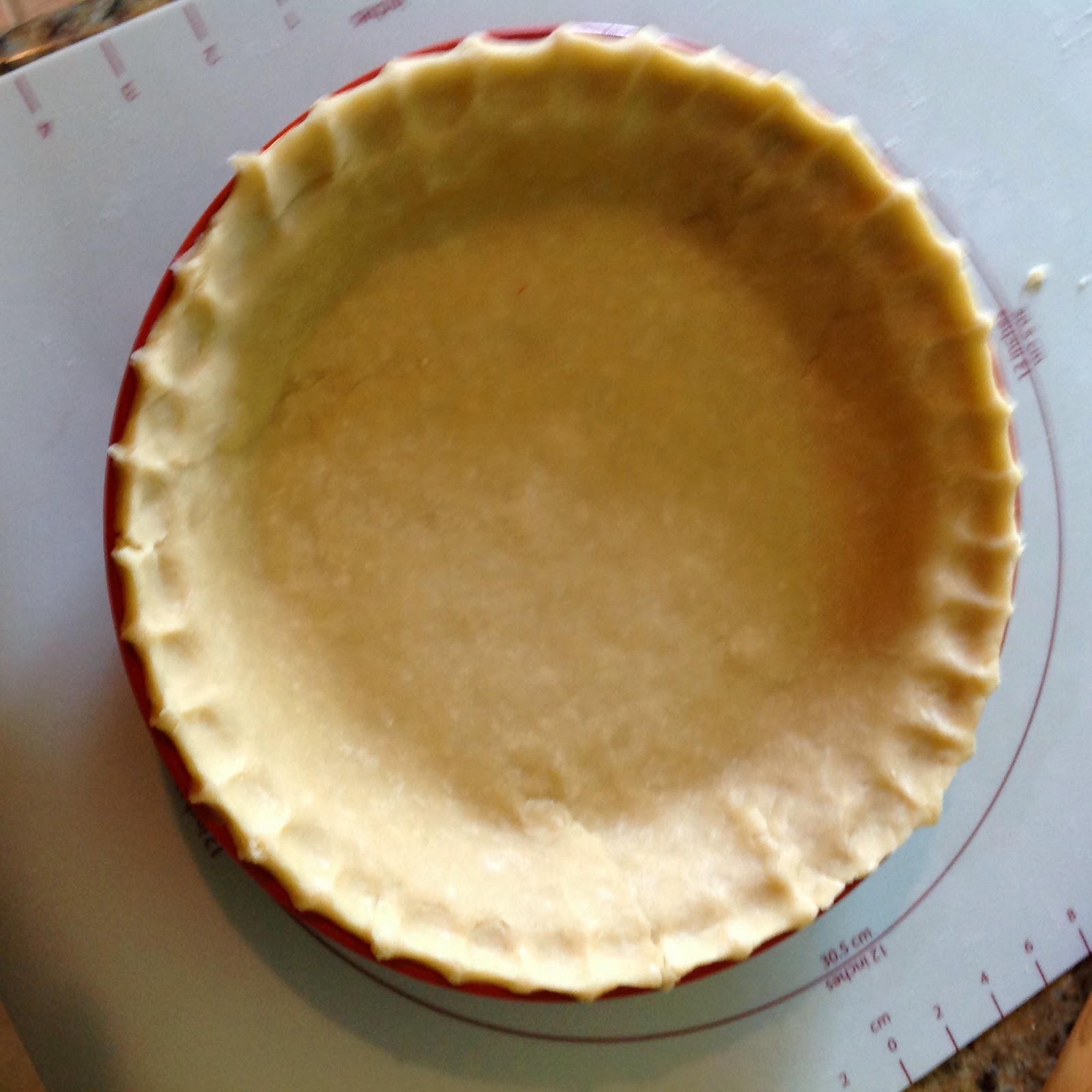 Flaky pie crust pastry in pie pan with fluted edges, ready for filling.