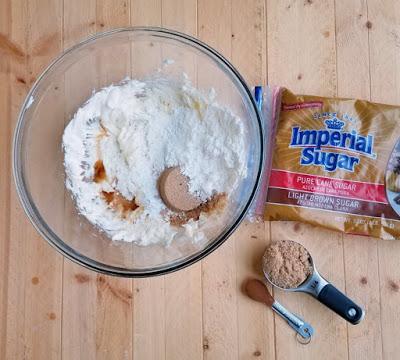 bowl of cinnamon brown sugar cream cheese frosting ingredients with measuring spoons etc.