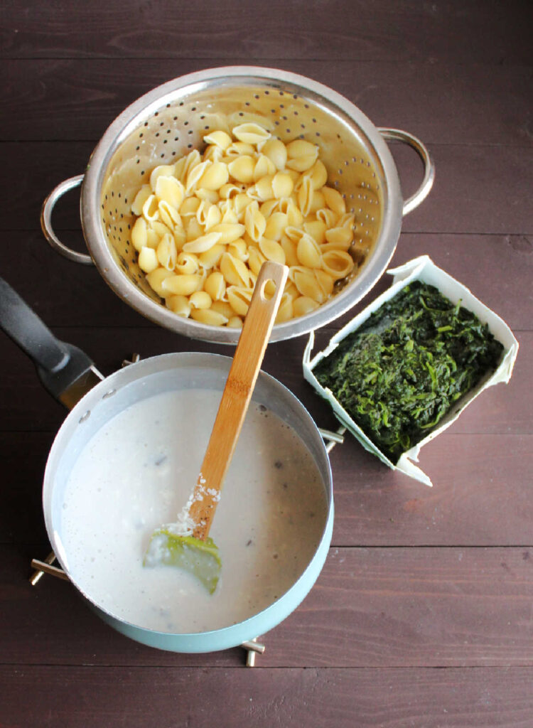 saucepan filled with white cheese sauce, colander filled with cooked shell pasta and box of defrosted chopped spinach.