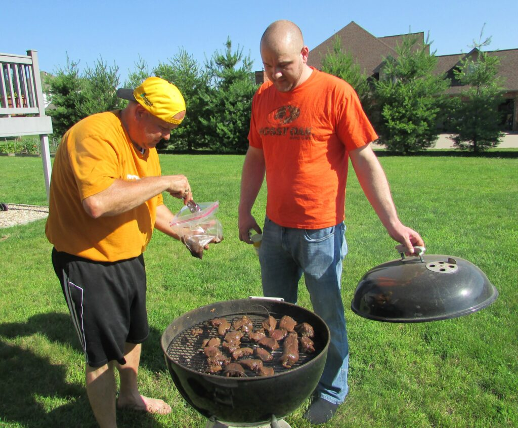 Dad and brother taking care of bul kogi backstrap on grill.