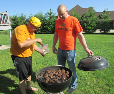 Pops and KC putting backstrap pieces on the grill