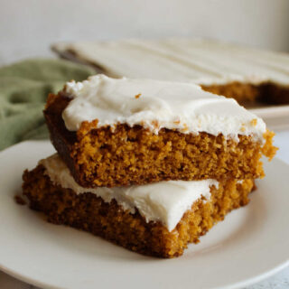 Stack of pumpkin bars with cream cheese frosting.