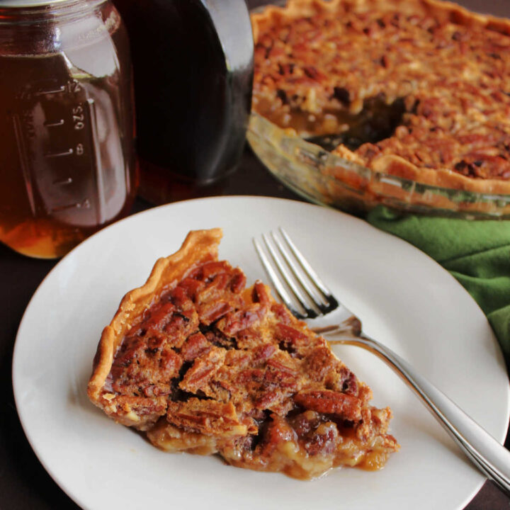 Slice of honey maple pecan pie with fork, ready to eat.
