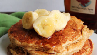 Close stack of banana pancakes with oatmeal and yogurt topped with banana slices and maple syrup.