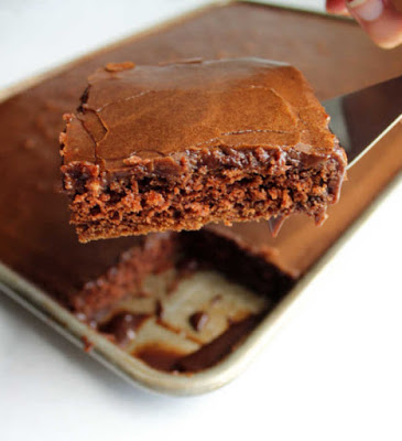 piece of chocolate texas sheet cake being lifted out of pan