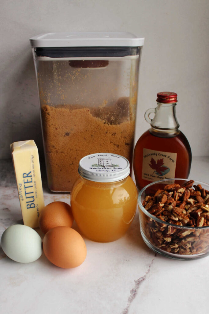 Ingredients for pecan pie made with maple syrup and honey.
