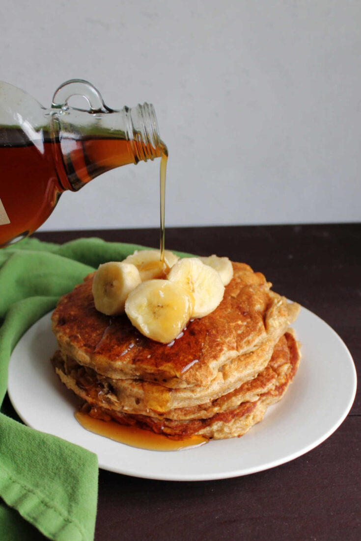 pouring maple syrup over stack of pancakes with sliced bananas on top.