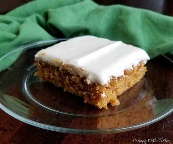 piece of pumpkin bars/cake with cream cheese frosting sitting on glass plate.
