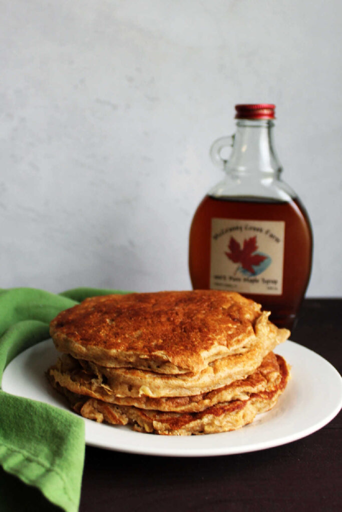 Stack of banana yogurt pancakes with jar of syrup in background.
