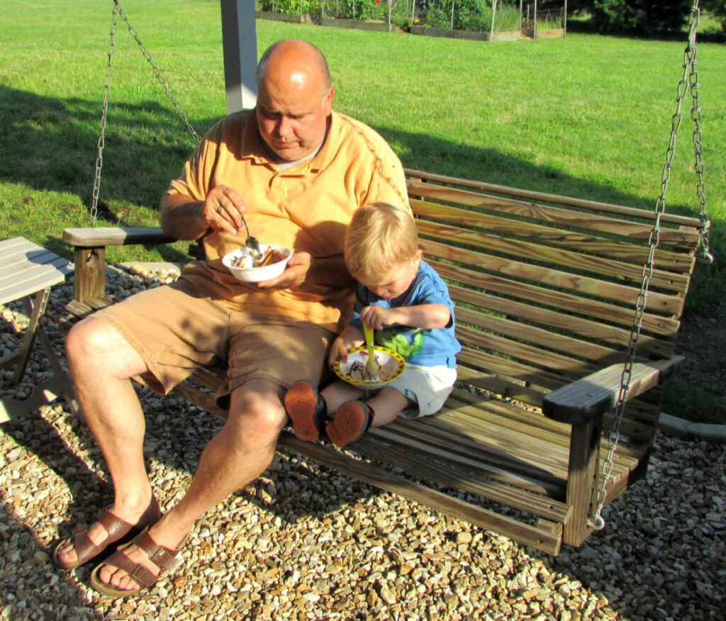 grandpa and grandson eating cake and ice cream on a porch swing.