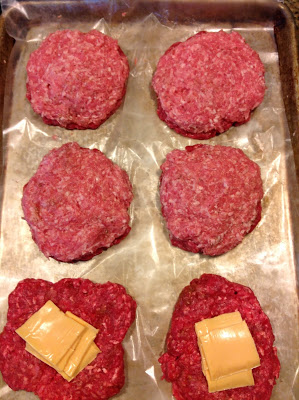 Two beef patties topped with cheese next two four more patties that have pork patties pressed on top for half beef half pork stuffed hamburgers.