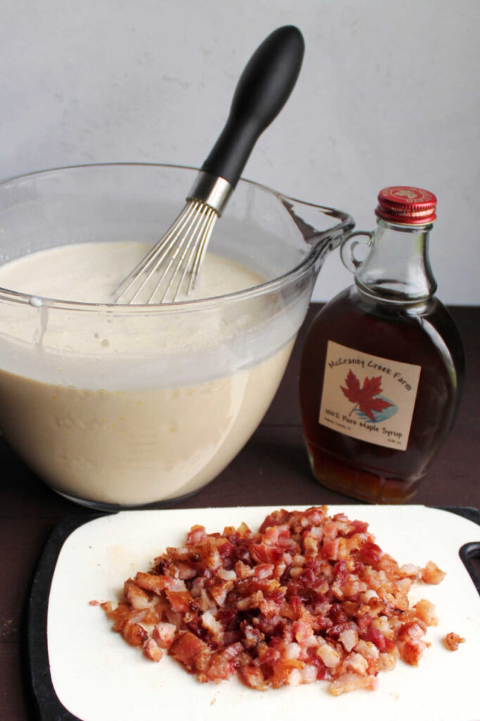 Big glass bowl of ice cream base next to a pile of chopped bacon and bottle of maple syrup.