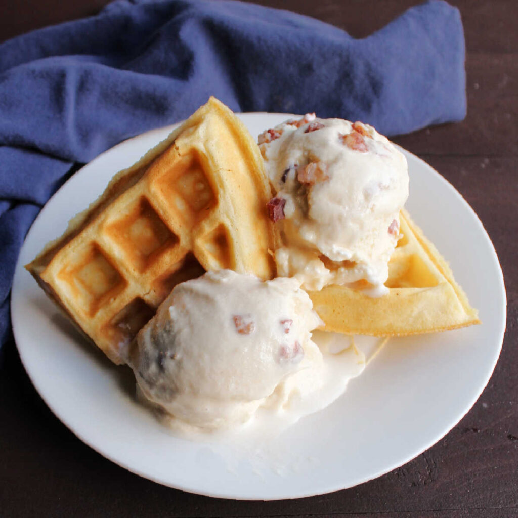 Plate of waffles with a couple of scoops of maple bacon ice cream.