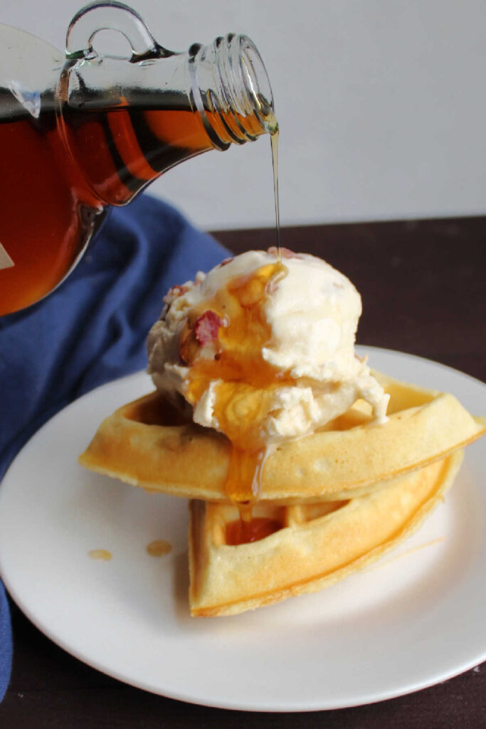 Pouring maple syrup over scoop of maple bacon ice cream perched on top of a couple pieces of Belgian waffle.
