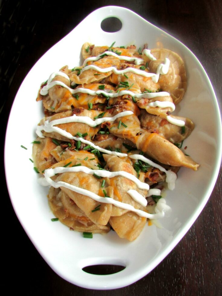 Large serving dish filled with homemade pierogi topped with cheese, chives and sour cream.