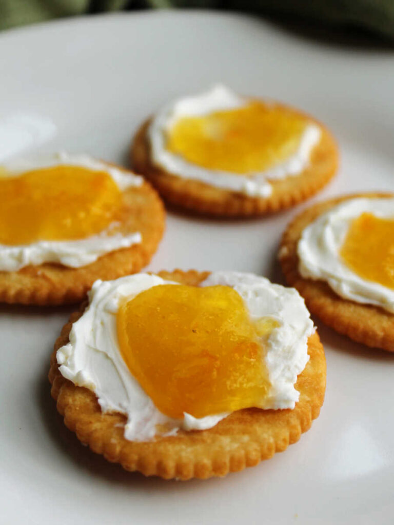 Crackers with a layer of cream cheese topped with peach habanero jelly.