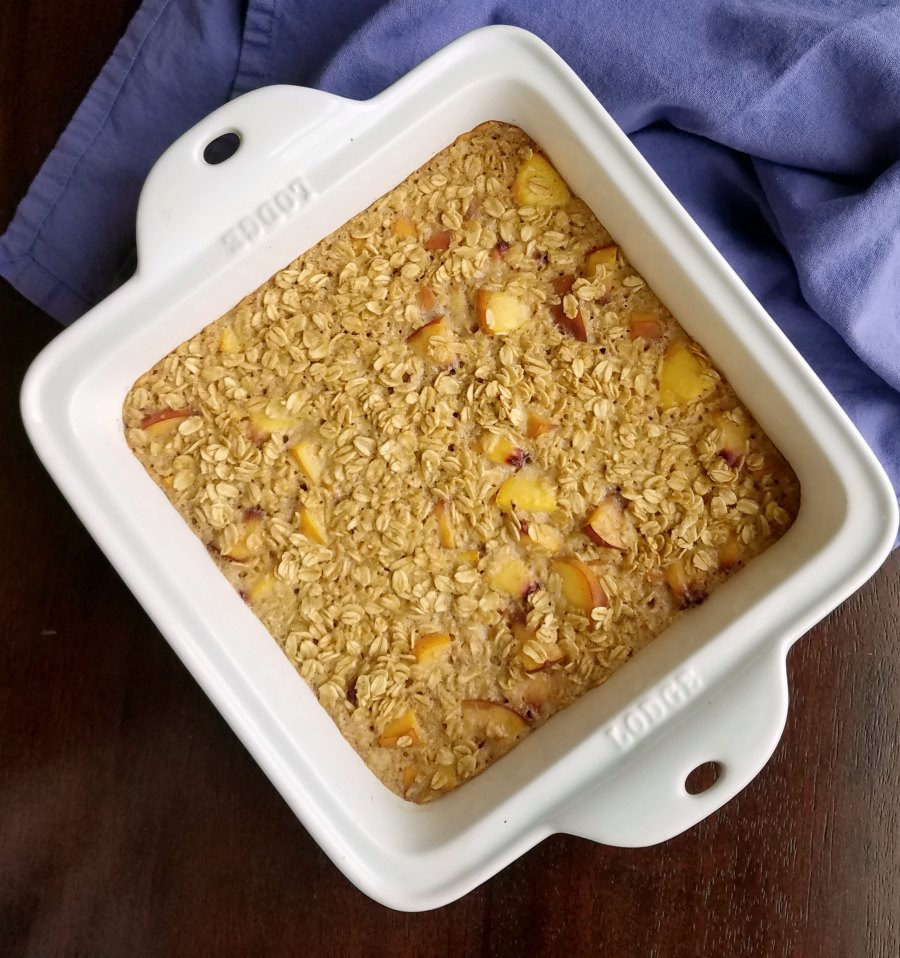 Square baking dish filled with freshly baked peaches and cream baked oatmeal.