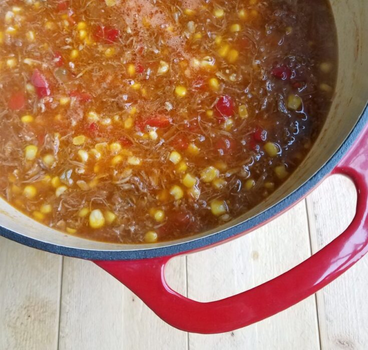 Enameled cast iron dutch oven filled with tomato based brunswick stew with pulled pork, chicken, brisket, and corn in it.