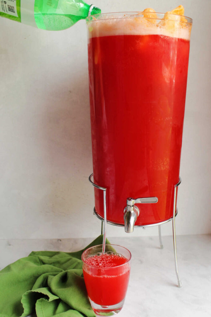 Pouring ginger ale into beverage dispenser filled with colorful punch and orange sherbet.