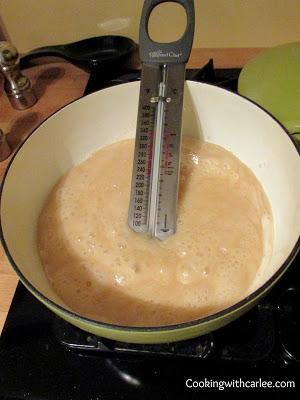 Caramel boiling in saucepan with candy thermometer.