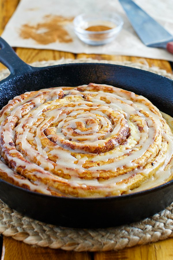 skillet filled with big pumpkin cinnamon roll that is drizzled with glaze.