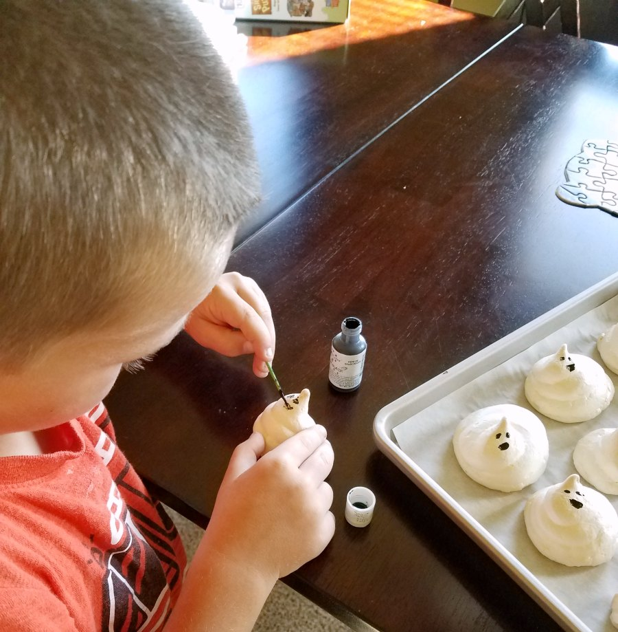 Little Dude using a toothpick to paint black food coloring gel faces on crisp meringue ghost cookies.