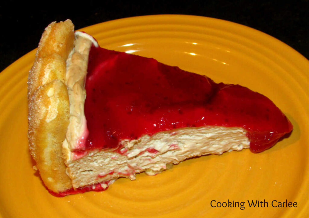 Slice of charlotte russe with creamy filling and cranberry topping.