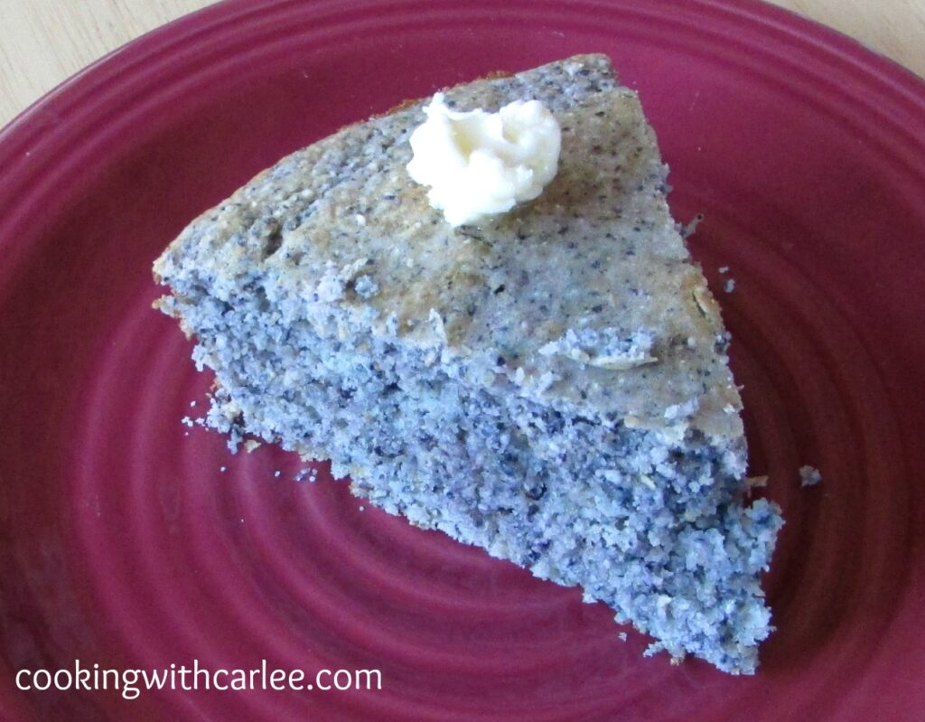 Slice of blue cornbread on plate with butter on top.