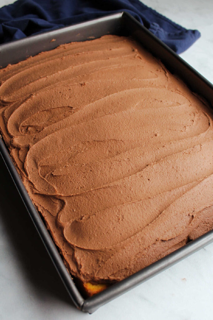chocolate brownie batter frosting spread over 9x13 inch cake with swirls left behind by spatula.
