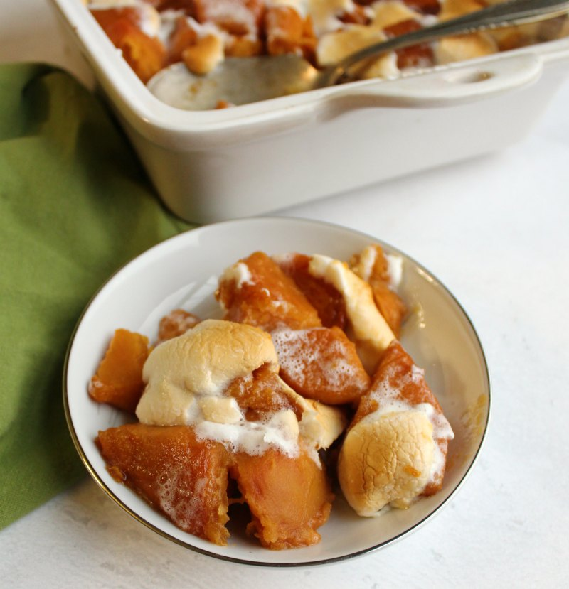 small dish of candied sweet potatoes with marshmallows in front of remaining pan.