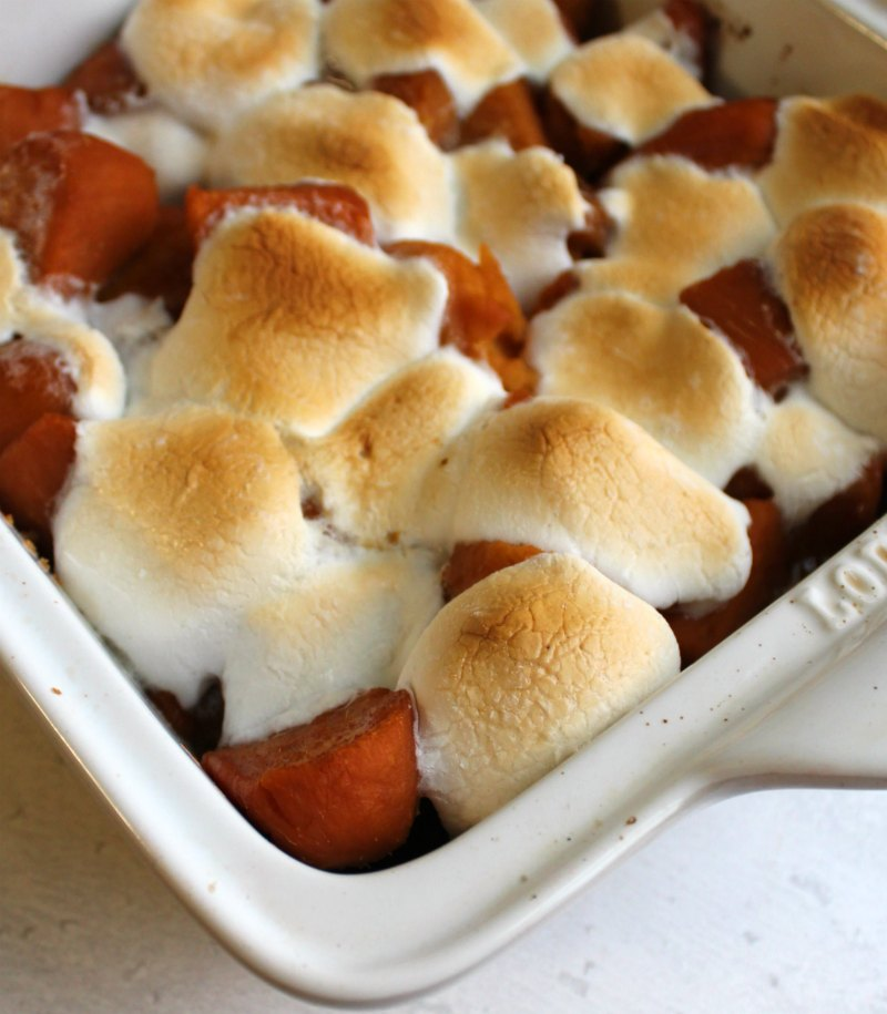 corner of pan filled with candied sweet potatoes topped with golden brown gooey marshmallows.