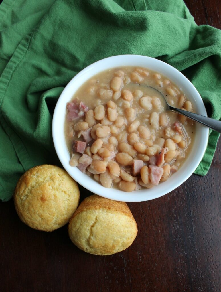 bowl of ham and beans next to corn muffins, ready to eat.