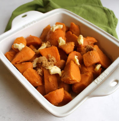 pan of sweet potatoes dotted with butter and brown sugar ready to bake