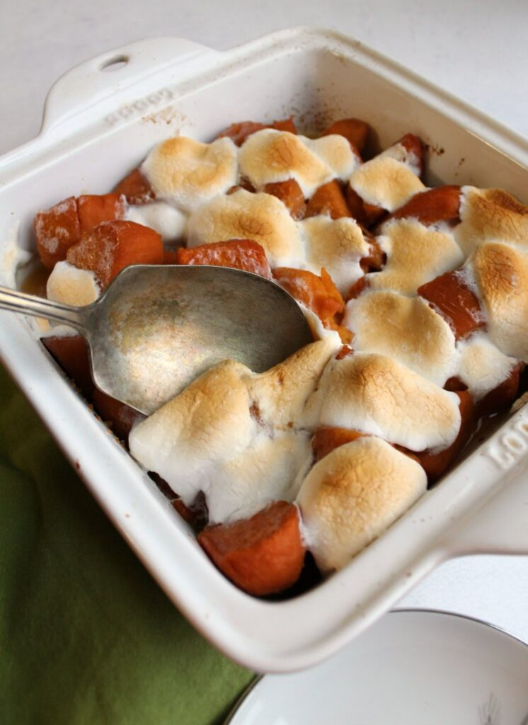 Spoon dipping into pan of marshmallow topped candied sweet potatoes.