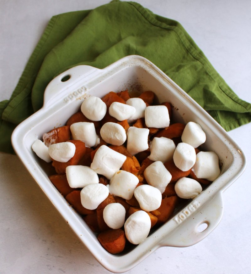 pan of sweet potatoes topped with raw marshmallows ready to bake.